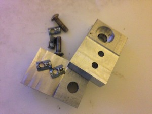 Milled aluminium in a block with two screw holes and a hole for a bearing and bolt
